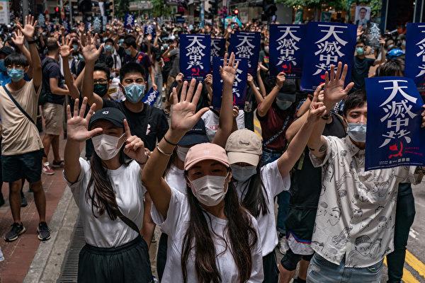 """Protest proti pekingskému návrhu zákona o národní bezpečnosti, v Hongkongu 24. května 2020. Protestující ukazují """"pět prstů"""", což má symbolizovat jejich """"pět požadavků"""" pro upevnění demokratických mechanismů v Hongkongu. (Anthony Wallace / AFP prostřednictvím Getty Images)"""